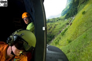 Flight engineer and mountain rescuer in the cabin of an Oryx helicopter, blurred landcape viewed through open door showing speed and angle of flight during a Joint SAAF-MCSA mountain rescue training exercise held in the Drakensberg.