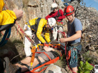 Training scenario: Patient fallen down short cliff, sustained head, neck and rib injuries. Hosted up on stretcher using tensioned backrope to assist with keeping the stretcher away from the cliff. The stretcher needed to be turned from horizontal to vertical to get it through the gully at the top of the cliff.