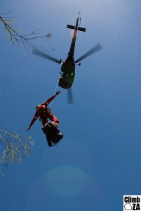 Rescuer being hoisted into an Alouette III helicopter