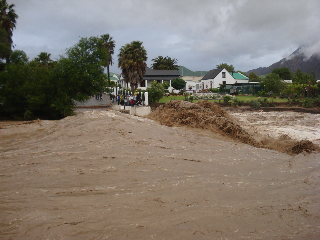 The suspension bridge is missing, it went at 04h00 Thursday morning, and the water just kept on coming. The whole of Montagu West was cut off from Montagu. We had no water, so the police set up a rope across the river at Lovers Lane crag and tied a pipe along it to get water across. The Spar sponsored bread and milk and then in the evening sent over food hampers, thanks Spar! We also got our supply of wine across, wow did we keep the spirits high